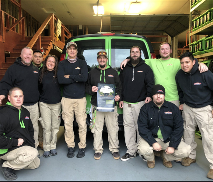A group of SERVPRO employees in a garage with a SERVPRO vehicle and equipment.