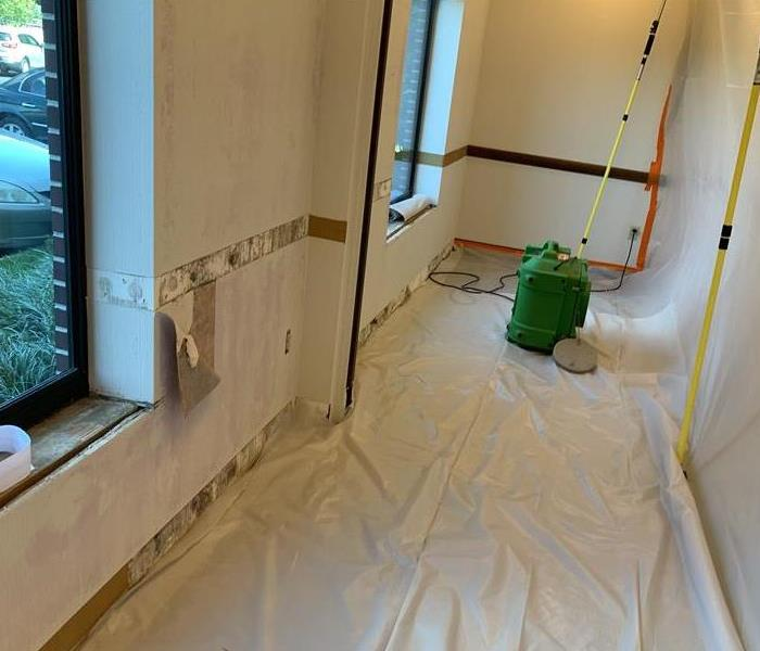 A hallway covered in white materials with SERVPRO equipment on the floor.
